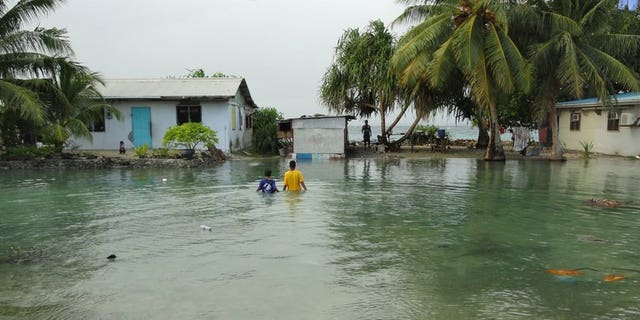 """Residents wade through flooding caused by high ocean tides in low-lying parts of Majuro Atoll, the capital of the Marshall Islands, on February 20, 2011. The Marshall Islands has warned of a Pacific """"climate catastrophe"""" that will wipe it off the map without decisive action on global warming, saying the next 12 months are critical."""