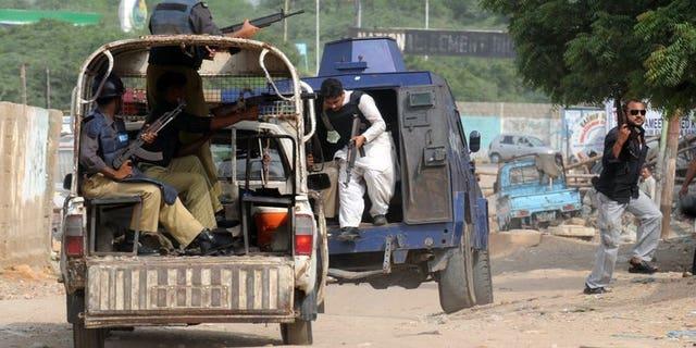 Pakistani police in vans patrol a troubled eastern neighbourhood of Karachi on August 4, 2010. Gunmen shot dead four policemen on a patrol in the southern Pakistani port city of Karachi Saturday, police said.