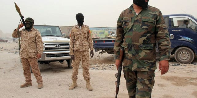 """Members of the Libyan Rapid intervention force unit patrol at a checkpoint in Benghazi on May 15, 2013. Libya's deputy prime minister Awadh al-Barassi announced his resignation late on Saturday, slamming the government as """"dysfunctional"""" and unable to end a wave of violence."""
