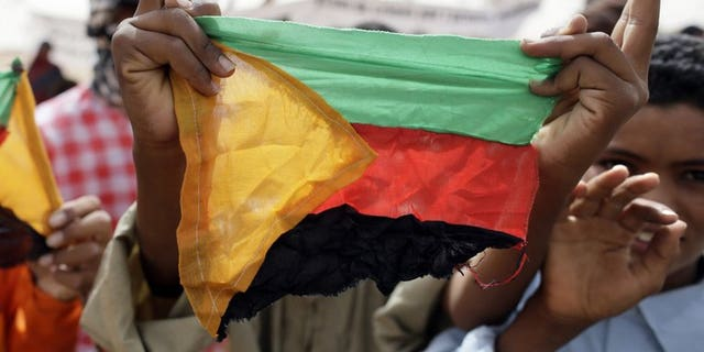 A Tuareg holds the flag of the National Movement for the Liberation of Azawad (MLNA) during a demonstration in Kidal on July 28, 2013. Tuareg rebels will fight Mali's newly-elected rulers if no negotiated solution is reached to grant their northern homeland of Azawad autonomy, a senior Tuareg rebel official warned.