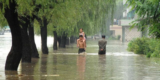 This file photo, taken by North Korea's official Korean Central News Agency in July, 2012, shows a road and houses being flooded at Anju city in South Phongan province, caused by typhoon and heavy downpour. Decades of deforestation and decrepit infrastructure have left N.Korea particularly vulnerable to floods, which led to some 170 deaths last summer.