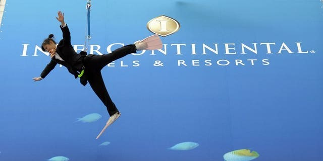 Performers dressed as divers hang off a wall during the opening ceremony for the InterContinental Hotels Group (IHG) hotel in Okinawa, Tokyo, on March 26, 2009. InterContinental Hotels Group on Tuesday announced a 25-percent increase in first-half net profits thanks to a strong showing by its American operations.