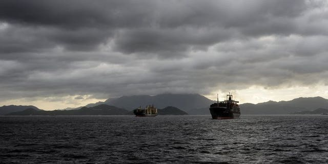 Cargo ships sail in heavy rains as a tropical storm passes over Hong Kong, on August 2, 2013. Helicopter teams have helped save all 21 crew from a cargo ship that sank off Hong Kong in a powerful typhoon that generated waves of up to 15 metres (50 feet).