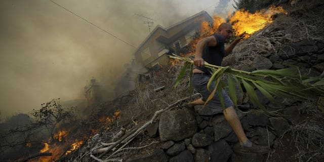 A man runs away from the flames as a wildfire rages near houses in Assomada, Madeira on July 21, 2012. A raging wildfire has prompted the evacuation of a hospital outside Funchal, capital of the Portuguese island of Madeira, officials said Saturday.