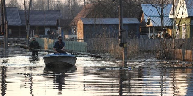 A man rows a boat across a flooded street during spring floodings in the suburb of the town of Bryansk, on April 19, 2013. More than 17,000 people have been evacuated in Russia's flood-hit Far East, a minister said Saturday, warning this figure could reach 100,000 as floodwaters wreak havoc across the region.