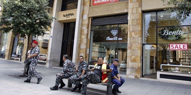 Members of the Internal security forces sit outside the Turkish Airlines offices in downtown Beirut on August 12, 2013. Lebanese authorities have arrested three suspects and charged them in connection with the abduction of two Turkish Airlines pilots, a judicial source told AFP on Saturday.