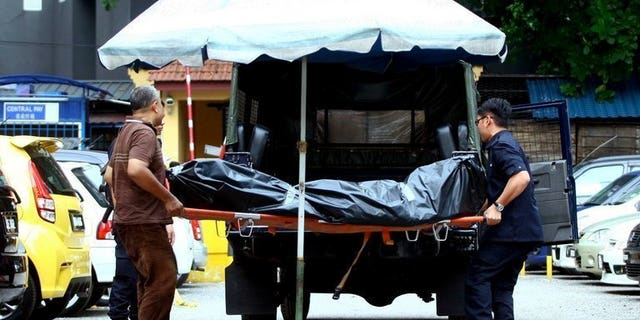 Picture taken on July 29, 2013 shows Malaysian forensic police carrying the body of late Arab Malaysian Banking Group founder Hussain Ahmad Najadi after he was shot dead on a street in Kuala Lumpur. Malaysian police said they killed five suspected gang members in a shootout early Monday and arrested 200 people in a crackdown on a spate of violent crime that has shocked the country.