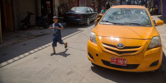 A boy runs past a taxi which was damaged by a bombing in the Allawi neighbourhood of central Baghdad on August 15, 2013. Attacks on Monday killed six people in Iraq, as gunmen defied massive government operations to stem some of the worst violence to have hit the country in five years.