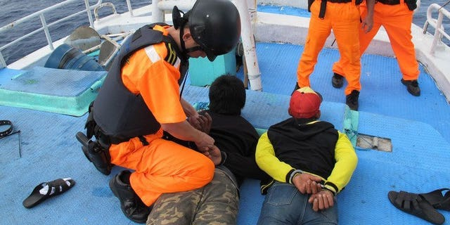 Undated photo released by Taiwan's Coast Guard Administration on August 20, 2013 shows Indonesian fishermen under arrest in the northeastern fishing port of Suao in Ilan. Nine Indonesian fishing boat crewmen suspected of murdering their Taiwanese captain and chief engineer faced an angry attack from relatives when they were brought back to the island on Tuesday to stand trial.