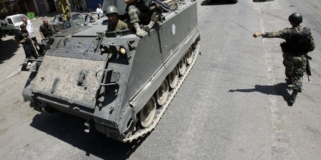 Lebanese army soldiers patrol Syria street in Tripoli's Sunni neighbourhood of Bab al-Tabbaneha on June 7, 2013. Two explosions went off within minutes of each other in the northern Lebanese city of Tripoli on Friday, an AFP photographer and the National News Agency reported.