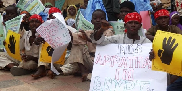 Young boys hold pro-Morsi placards during a protest on August 24, 2013 in Sheikh Ahmad Tijjani mosque, Kano, Nigeria. Thousands rallied peacefully in northern Nigeria to demand the return of Egypt's Islamist former president Mohamed Morsi, ousted by the military early last month.