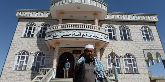 Local men stand in front of a Shiite mosque where intelligence forces killed two Pakistani terrorists in police uniforms, in Kabul, on September 5, 2013. Afghan intelligence agency said on Thursday that its spies shot dead two Pakistanis who opened fire on the worshippers before dawn at the mosque.