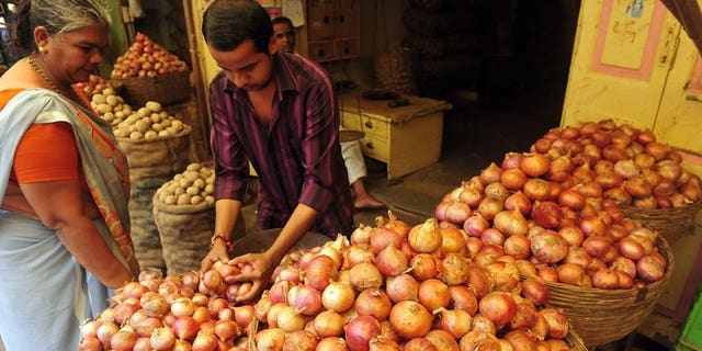 """A customer looks on as a shop assistant selects onions for her at a market in Mumbai on August 22, 2013. A US-based website offering onions at heavily discounted prices in India has seen an """"overwhelming"""" response as consumers there reel from sky-rocketing prices of the vegetable."""