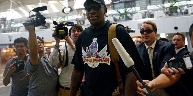 Former US NBA basketball player Dennis Rodman (C) is surrounded by members of the media as he makes his way through Beijing's international airport on September 3, 2013.