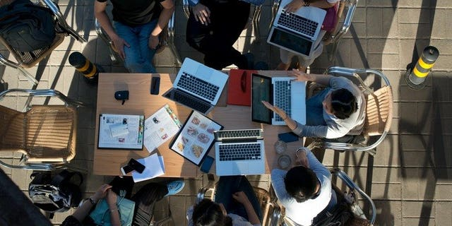 """People sit around laptop computers at a cafe in Beijing on May 29, 2013. Chinese Internet users could face three years in prison for writing defamatory messages that are then re-posted 500 times under regulations announced amid a broader crackdown on """"online rumours""""."""
