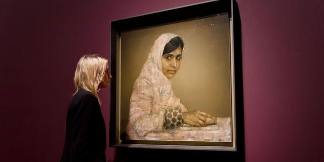A gallery worker poses with a painted portrait of Malala Yousafzai, the teenage Pakistani advocate for girls education who was shot in the head by the Taliban in 2012, by Jonathan Yeo at the National Portrait Gallery in central London on September 10, 2013.