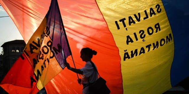 """A protester holds a flag reading """"Save Rosia Montana"""" during demonstrations in Bucharest against the Rosia Montana Gold Corporation (RMGC), a Canadian gold mine project using cyanide,on September 8, 2013."""