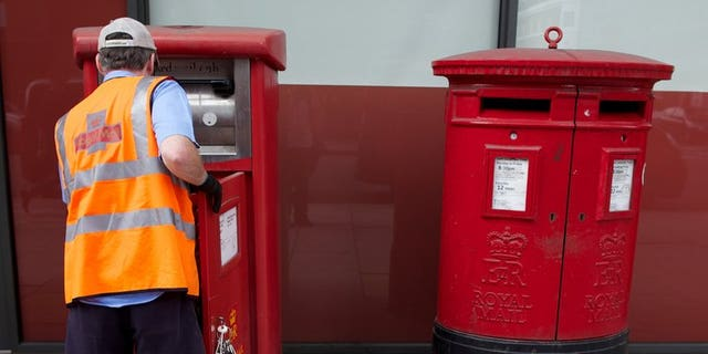 A postman empties a Royal Mail post box in London on July 10, 2013. Part sale of Royal Mail could be worth up to ??3.0 billion ($4.74 billion, 3.57 billion euros), reports say. The government previously said that it would take on Royal Mail's historic pension deficit.