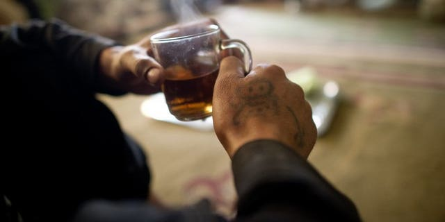 """A man drinks tea in Kabul on April 24, 2012. An Indian court has reprimanded police for arresting a man they accused of drinking tea in a """"suspicious"""" manner at one of the country's ubiquitous roadside stalls."""