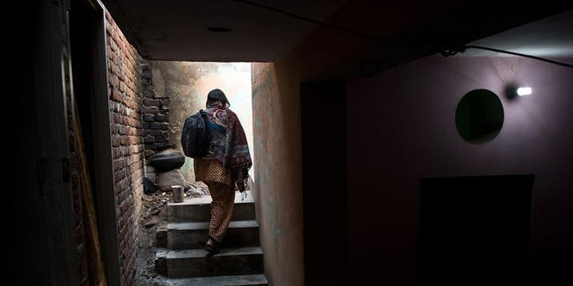 """A woman walks up stairs in Haryana state, India, on January 23, 2013. A man was beheaded and his girlfriend beaten to death in an """"honour killing"""" in northern India after they eloped, police said Thursday."""