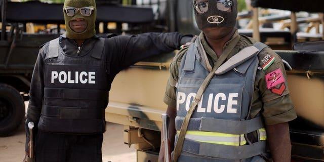 Nigerian police in Borno state pose prior to a patrol in former Boko Haram headquarters in Maiduguri on June 5, 2013.