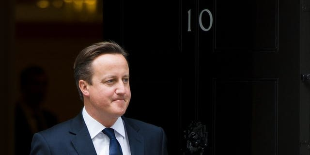 Prime Minister David Cameron, stands outside 10 Downing Street, central London on September 18, 2013. Facing the prospect of a family wedding just hours after a gruelling G20 summit, Cameron grabbed forty winks on a bed -- unaware that his sister-in-law was posing for the camera in front of him.