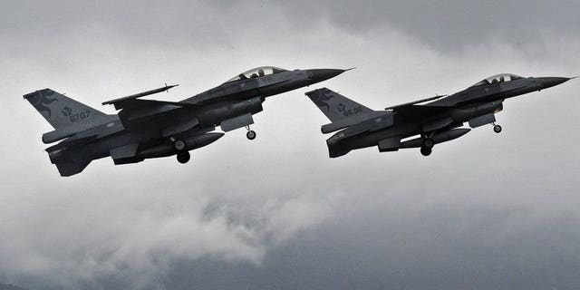 """Two F-16 fighters take-off from the Hualien air force base in eastern Taiwan, on January 23, 2013. Taiwan's air force will be armed with """"smart"""" munitions before the year's end that could be used against any Chinese invasion by striking airfields and harbours on the mainland, according to a report in the China Times."""