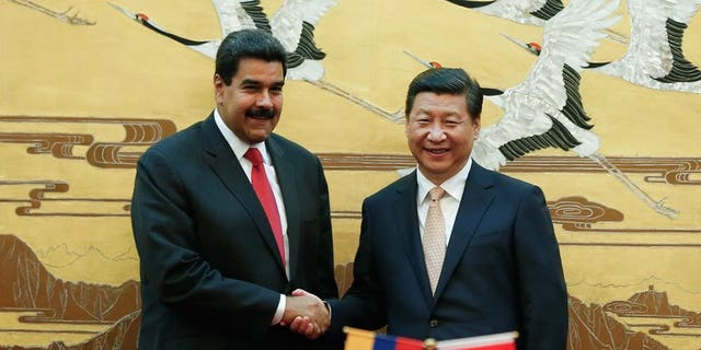 Chinese President Xi Jinping (right) shakes hands with his Venezuelan counterpart Nicolas Maduro during a signing ceremony at the Great Hall of People in Beijing, on September 22, 2013. Maduro says Beijing has granted his country a $5 billion credit line.