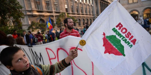 """A child waves a flag with the logo of """"Save Rosia Montana"""" NGO during the 22nd day of demonstrations in Bucharest against the Rosia Montana Gold Corporation (RMGC), a Canadian gold mine project using cyanide, on September 22, 2013."""