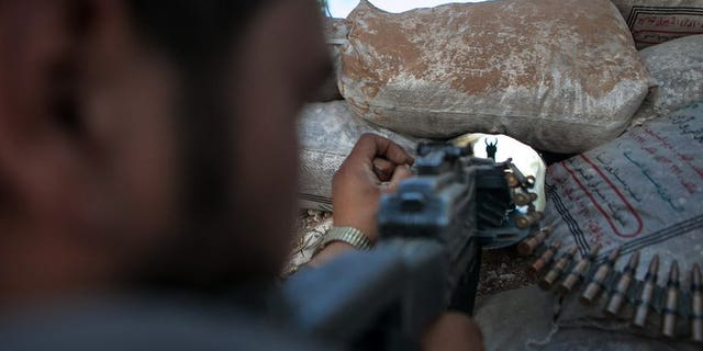 A Syrian rebel fighter points his rifle through a hole in sandbags on June 14, 2013 in Idlib.