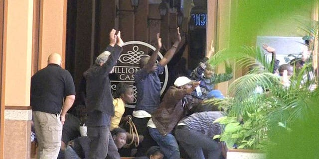 Civilians are evacuated from a shopping mall following an attack by masked gunmen in Nairobi on September 21, 2013. An alleged commander in the Somali Shebab rebel group has denied press reports that Westerners or women were involved in the hostage standoff at a Nairobi mall that has killed at least 69 people.