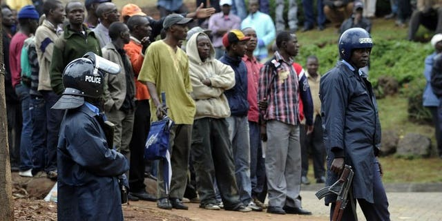 Armed Kenyan policemen keep onlookers away outside the Westgate mall in Nairobi on September 23, 2013. A fourth Briton has been confirmed killed in an attack at the shopping mall staged by Somali Islamist militants, the Foreign Office in London has said.