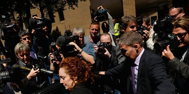 Members of the media surround former News International chief executive Rebekah Brooks in London on June 5, 2013 after attending a hearing into charges linked to the phone-hacking scandal. A member of staff at London's Metropolitan Police headquarters was one of two people arrested on Tuesday as part of a bribery investigation sparked by the phone-hacking scandal at the News of the World tabloid.