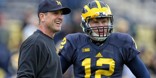 Oct 17, 2015; Ann Arbor, MI, USA; Michigan Wolverines head coach Jim Harbaugh talks to Michigan Wolverines quarterback Alex Malzone (12) prior to a game against the Michigan State Spartans at Michigan Stadium. Mandatory Credit: Mike Carter-USA TODAY Sports