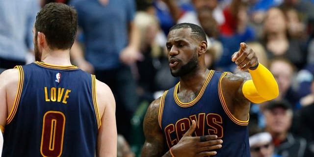 Mar 10, 2015; Dallas, TX, USA; Cleveland Cavaliers forward LeBron James (23) talks with forward Kevin Love (0) during a timeout from the game against the Dallas Mavericks at American Airlines Center. The Cavs beat the Mavs 127-94. Mandatory Credit: Matthew Emmons-USA TODAY Sports