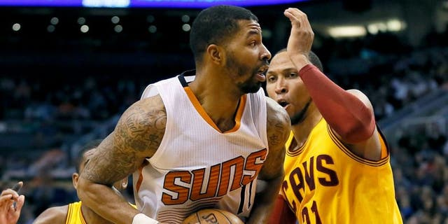 Phoenix Suns' Markieff Morris drives against Cleveland Cavaliers' Shawn Marion during the second half of an NBA basketball game, Tuesday, Jan. 13, 2015, in Phoenix. The Suns won 107-100. (AP Photo/Matt York)