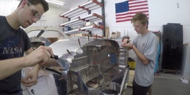 High school senior Brian Zelt and incoming university freshman Chase Cook work with other students on building an airplane.