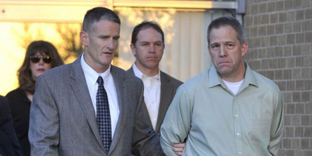 JetBlue pilot Clayton Frederick Osbon, (r.), is escorted by FBI agents after a 2012 incident in which he ran out of the cockpit screaming and terrifying passengers.