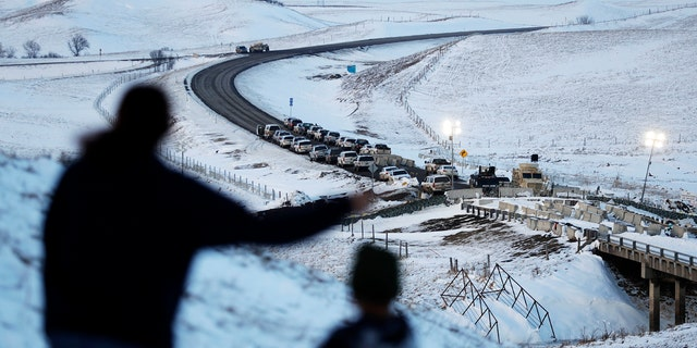 Law enforcement vehicles line a road leading to a blocked bridge next to the Oceti Sakowin camp where people have gathered to protest the Dakota Access oil pipeline in Cannon Ball, N.D., Saturday, Dec. 3, 2016.