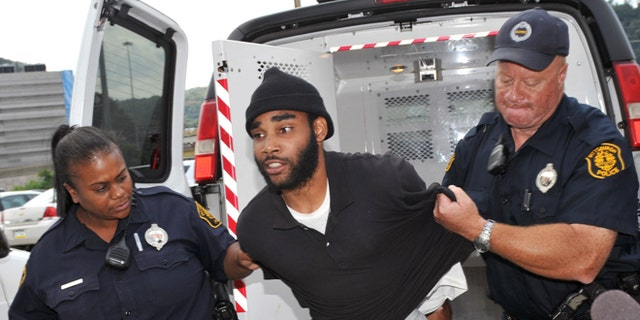 Sept. 21, 2012: Klein Michael Thaxton, center, is lead into Pittsburgh Police headquarters after being apprehended without incident at Three Gateway Center in Pittsburgh.