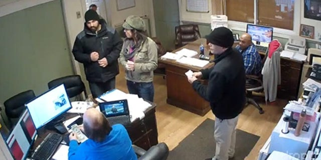 Security footage show pizza delivery man Jarrid Tansey inside a Massachusetts car dealership office.
