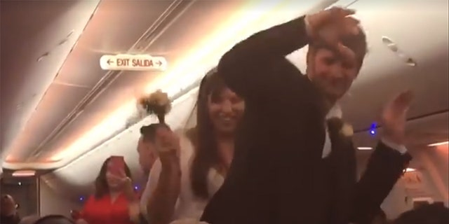 After the nuptials, the couple danced down the aisle with the flight crew.