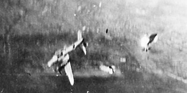 """Photo shows """"Hell's Fury"""" after it was hit by enemy flak. The left engine and nacelle are on fire after the left wing was blown off."""
