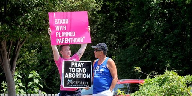 FILE -- July 28, 2015: Andrew Ward, left, and Bill Pauls discuss their positions on abortion during a rally across the street from the Planned Parenthood of Kansas and Mid-Missouri in Columbia, Mo. (Don Shrubshell/Columbia Daily Tribune via AP)