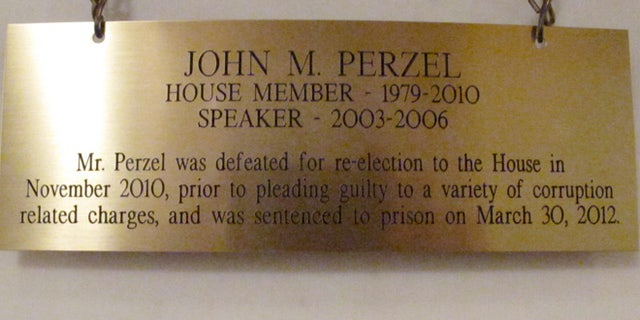 The plaque hanging in the Pennsylvania Capitol below the official portrait of former House Speaker John Perzel and three other former top state lawmakers in Harrisburg, Pa., now includes information about their criminal histories.  Plaques that add those details to the dates the four men served were hung Tuesday, July 15, 2014.  (AP Photo/Marc Levy)