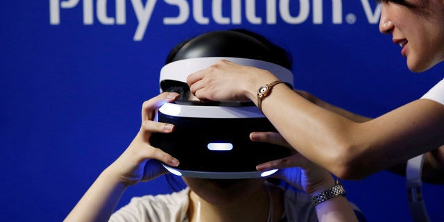 A hostess helps a woman to wear Sony's PlayStation VR headset at Tokyo Game Show 2016 in Chiba, east of Tokyo, Japan, Sept. 15, 2016. (REUTERS/Kim Kyung-Hoon/File Photo)
