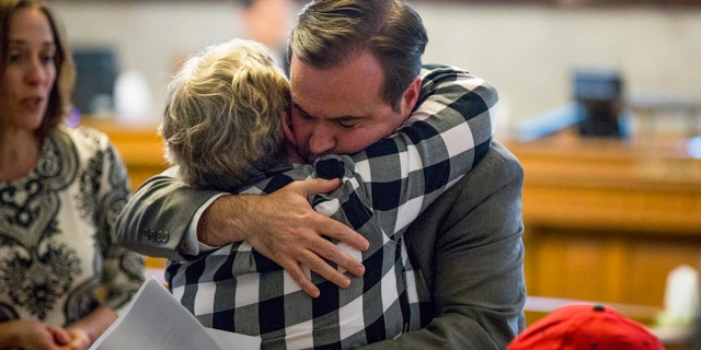 In a Tuesday, April 17, 2018 photo, Cincinatti Mayor John Cranley hugs a member of Kyle Plush's family before the council's Law and Public Safety Committee.