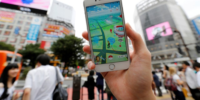 """File photo - A man poses with his mobile phone displaying the augmented reality mobile game """"Pokemon Go"""" by Nintendo in front of a busy crossing in Shibuya district in Tokyo, Japan, July 22, 2016. (REUTERS/Toru Hanai)"""