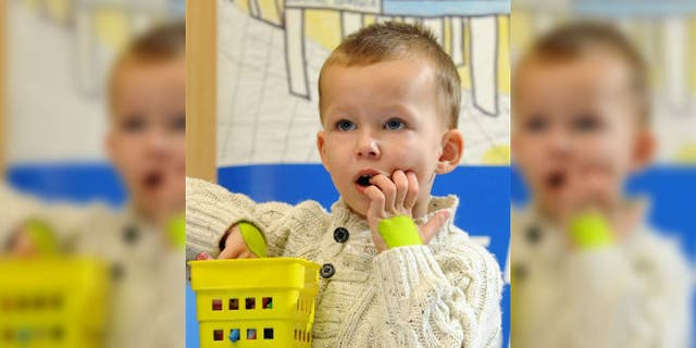 Toddler Adam, 2 years 6 months, plays during a press conference ending his 74 days treatment in University Children's Hospital, in Krakow, Poland, Thursday, Feb. 12, 2015. (AP Photo/Alik Keplicz)