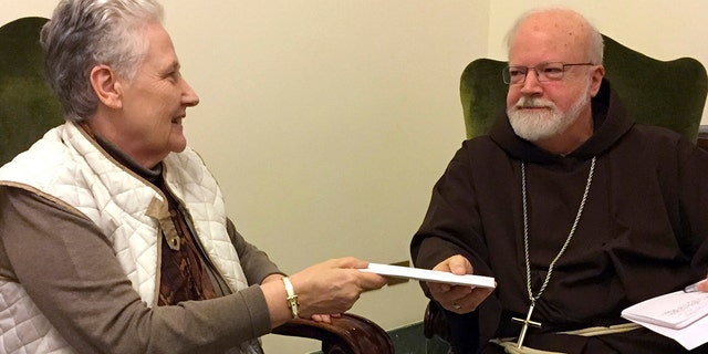 Marie Collins, a member of the pope's sex-abuse commission, hands a letter to Cardinal Sean O'Malley detailing the abuse of Juan Carlos Cruz and a cover-up by Chilean church authorities, at the Domus Santa Marta on April 12, 2015.